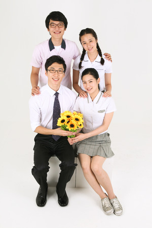 arm bouquet: Three Asian students and a teacher gethering in the studio, isolated on white.