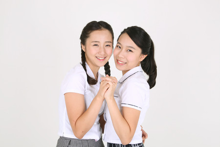 nobleness: Two Asian girl students holding hands and facing each other lovely in the studio, isolated on white.