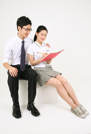 An Asian girl listending and writing something on her note book and her teacher sitting next to her in the studio, isolated on white.
