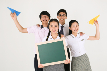 Two Asian girls holding a black board and a paper airplace and a boy holding a paper airplane and their teacher standing behind in the studio, isolated on white Stock Photo