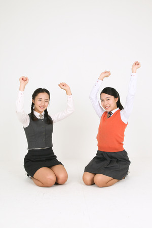 Two Asian girl students receving punishment but they smiling in the studio, isolated on white.
