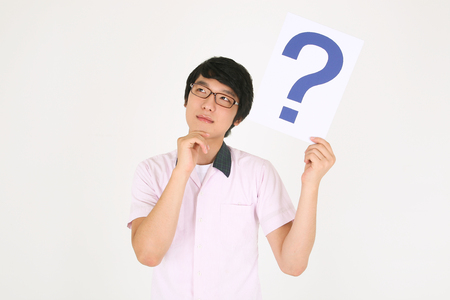 An Asian boy student holding a question mark sign and wondering in the studio, isolated on white.