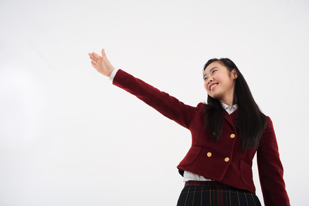 Young Asian girl student with uniforms outfit in the studio, isolated on white Stock Photo