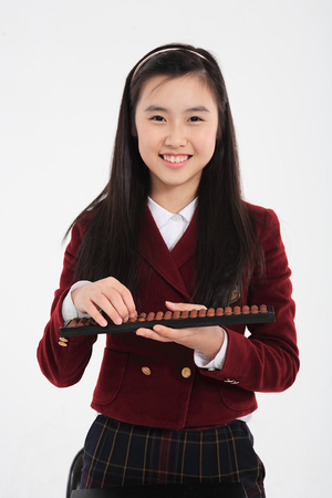 Young Asian girl student with an abacus in the studio, isolated on white Stock Photo
