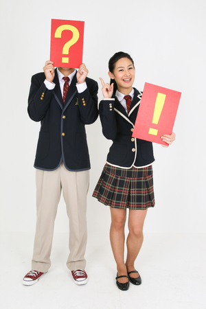 An Asian girl and a boy students holding exclamation mark and question mark sign in the studio, isolated on white.
