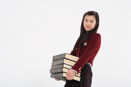 Young Asian girl student with stack of books in the studio, isolated on white