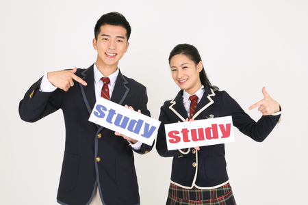 An Asian girl and a boy students holding a study sign in the studio, isolated on white.