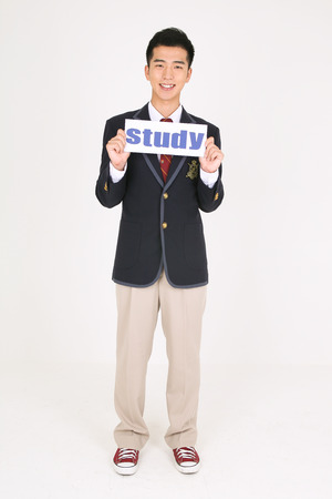 An Asian boy student holding a study sign with smile in the studio, isolated on white. Stock Photo