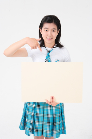An Asian girl student with a board in the studio, isolated on white.