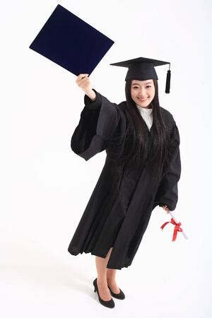 An Asian woman with a graduation hat and clothes in the studio, isolated on white Stock Photo