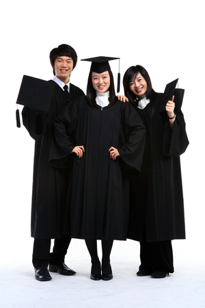Two Asian women and a man with a graduation hat and clothes in the studio, isolated on white.