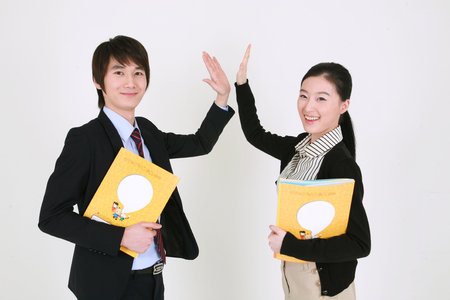 Well dressed young Asian couple holding books and giving high five - isolated on white 版權商用圖片