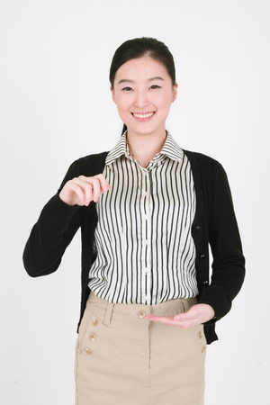mladistvý: Well dressed young Asian woman holding an invisible board - isolated on white