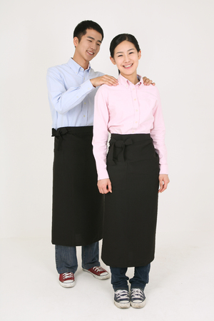 Young Asian waitress and waiter in a studio - isolated on white Stock Photo