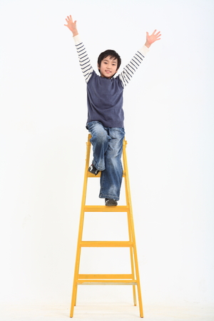 hurray: A asian boy posing leaning ladder - isolated on white