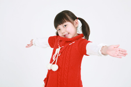 earned: A little asian girl posing with both hands outstretched - isolated on white