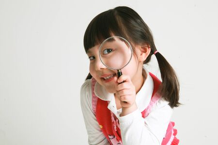 A little asian girl posing with magnifying glass - isolated on white