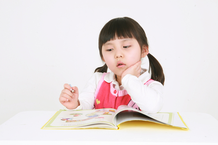 A little asian girl studying - isolated on white Stock Photo