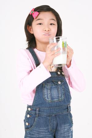 牛乳のグラスで飲むアジアの女の子 - 白で孤立 写真素材