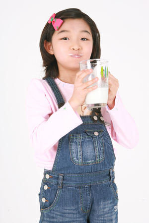 A asian girl drinking with glass of milk - isolated on white