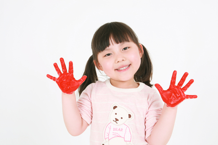A little asian girl posing with paints palms - isolated on white