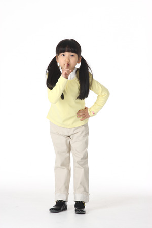 An Asian girl shushing with her finger - isolated on white