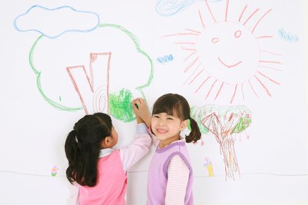 pert: Two Asian girls painting on the wall and smiling - isolated on white Stock Photo