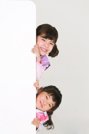 Two Asian girls standing behind the wall - isolated on white