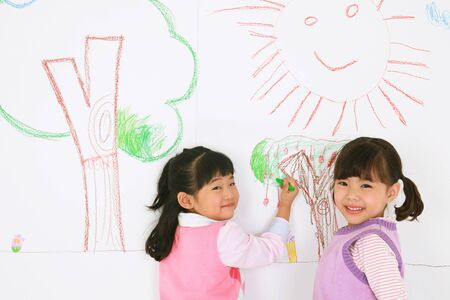 Two Asian girls painting on the wall and smiling - isolated on white Stock Photo