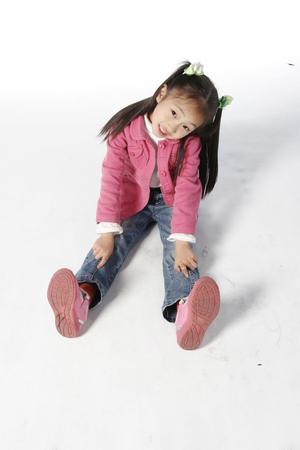 백인에 고립 된 바닥에 앉아있는 아시아 소녀