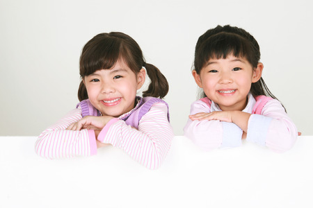 Two Asian girls looking at camera, smiling - isolated on white