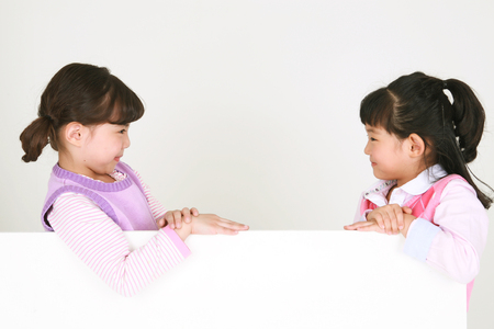 Two Asian girls looking at the opposite - isolated on white Stock Photo