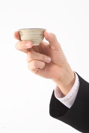 ショットのカップを持っている手のクローズ アップ ショット 写真素材