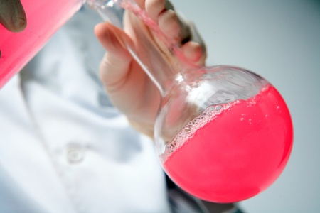 additional chemicals: Close-up shot of hands holding flasks Stock Photo