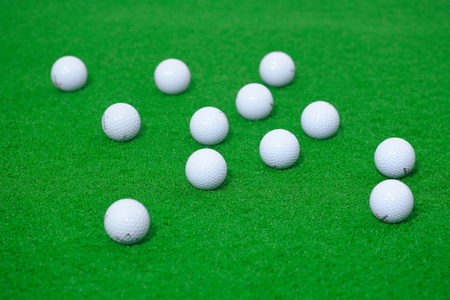 Close-up shot of golf balls lying on the field