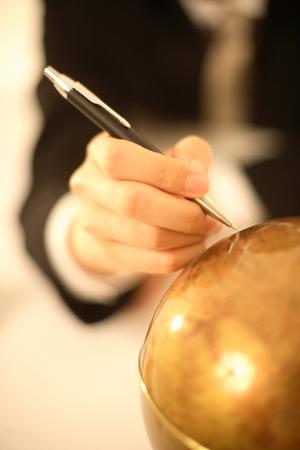 mark pen: Man marking on a globe Stock Photo