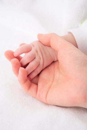 Mom holding a babys hand Stock fotó