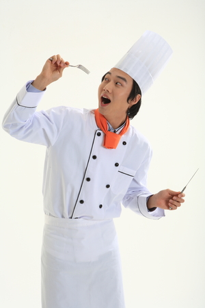 A male cook holding a silver knife and fork
