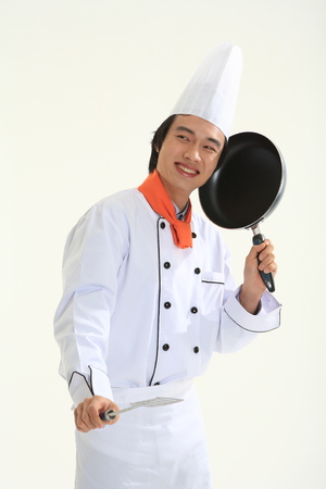 A male cook holding a pan with a spatula