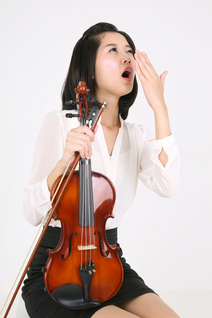 violinista: A female violinist yawning as holding a violin and a bow Foto de archivo