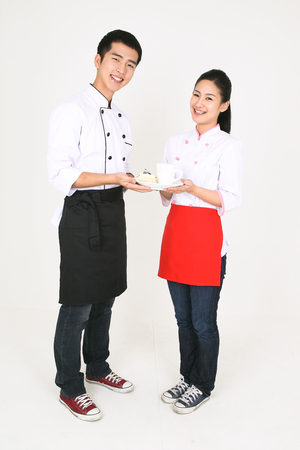 sho: A male cook and a female cook holding a cup of coffee and a piece of cake