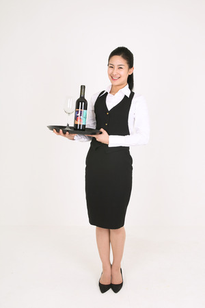 A female waitress with a bottle of wine and a glass Imagens