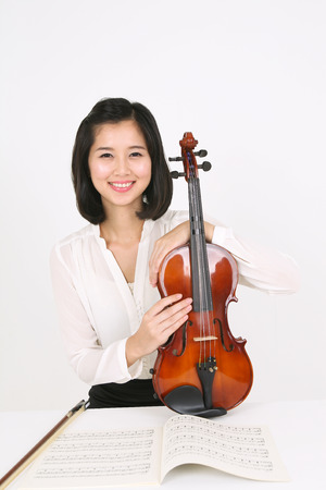 A female violinist sitting at the desk as holding a violin in arms