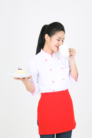 A female cook carrying a cup of coffee and a piece of cake each hand