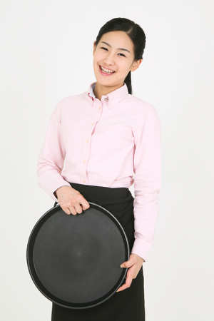 A young waitress holding a tray Stock Photo