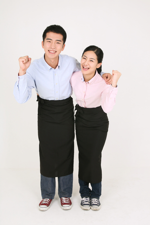 A waiter and a waitress putting arms around on each other