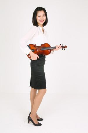 instrumentalist: A female violinist holding a violin like a guitar Stock Photo