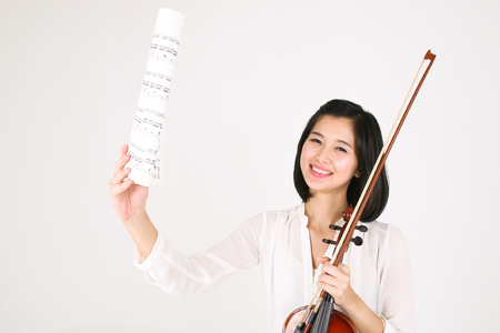 instrumentalist: A female violinist holding musical notes Stock Photo