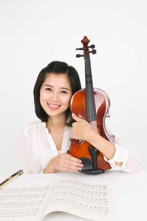 gifted: A female violinist sitting at the desk as holding a violin in arms