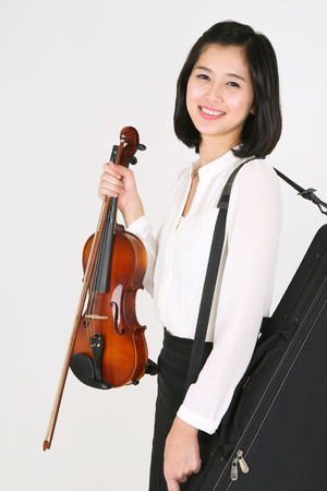 violinista: A female violinist holding a violin and a bow as carrying a violin case on shoulder Foto de archivo